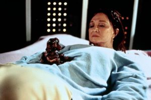 Diane Ladd looking dolefully at a bloody dinosaur emerging from her uterus.